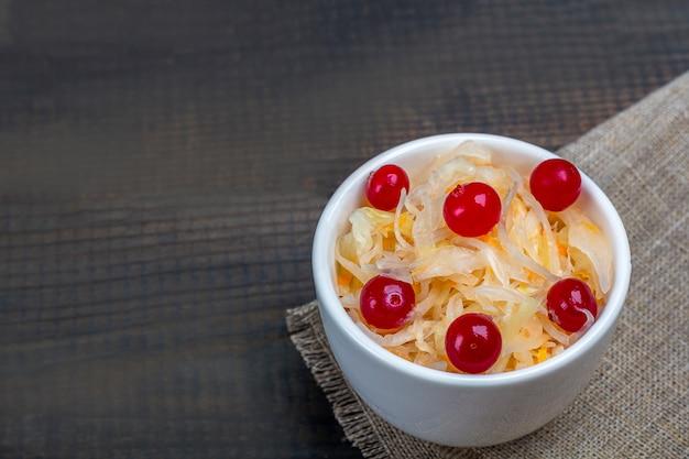 소박한 나무 테이블에 그릇에 크랜베리와 발효 양배추