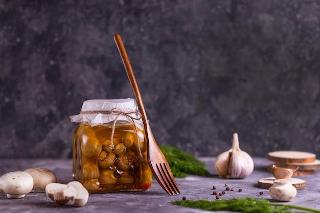 Ферментированные консервированные грибы шампиньоны в стеклянной банке с чесноком, лавровым листом и укропом на деревянных подставках