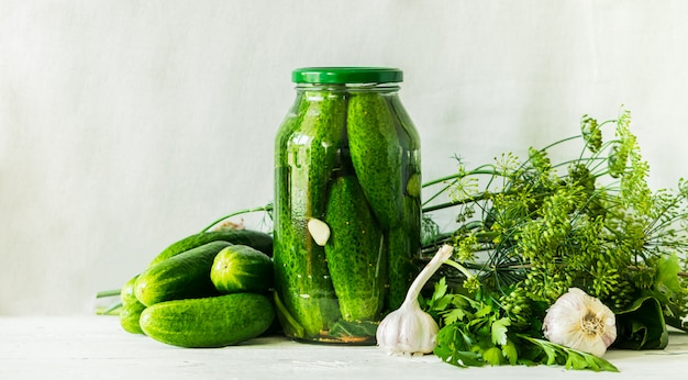 Fermented or canning cucumbers in glass jar on table processing of the autumn harvest. canned food