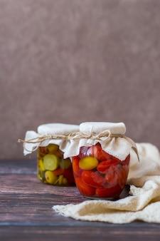 Ферментированные помидоры черри и салат из маринованных огурцов в стеклянных банках на деревянном фоне вертикально