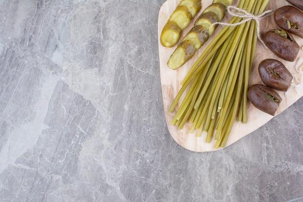 Ферментированные огурцы, баклажаны и стручковая фасоль на деревянной доске.