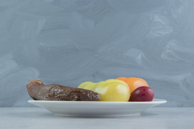 하얀 접시에 발효된 가지와 토마토입니다.