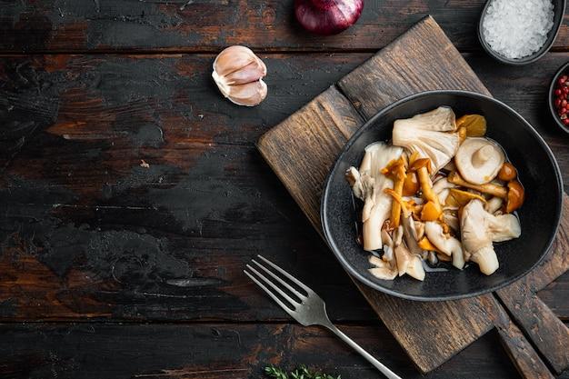 Ферментированная пища: набор для консервирования грибов, на фоне старого темного деревянного стола, плоская планировка, вид сверху, с пространством для текста.