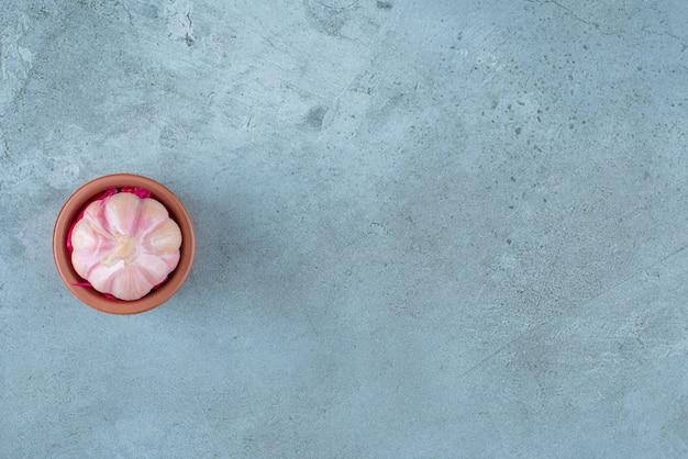 Aglio fermentato in una ciotola, sul tavolo blu.