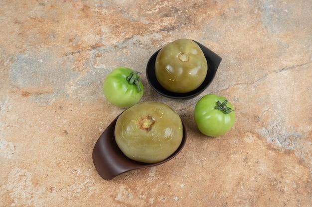 Pomodori verdi fermentati in ciotole nere con pomodori freschi