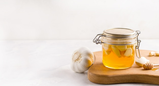 Ферментированный мед с чесноком на светлом фоне. скопируйте пространство. баннер