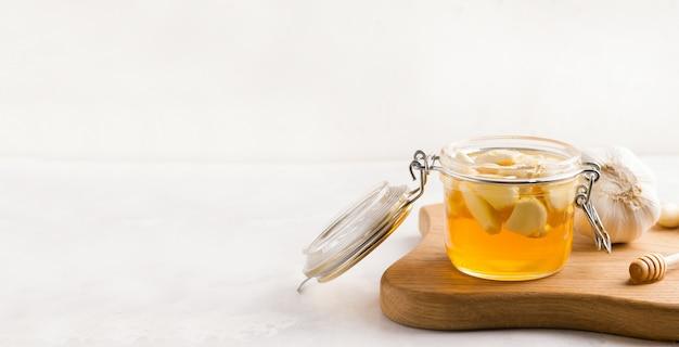 Ферментированный мед с чесноком на деревянной доске. скопируйте пространство. баннер