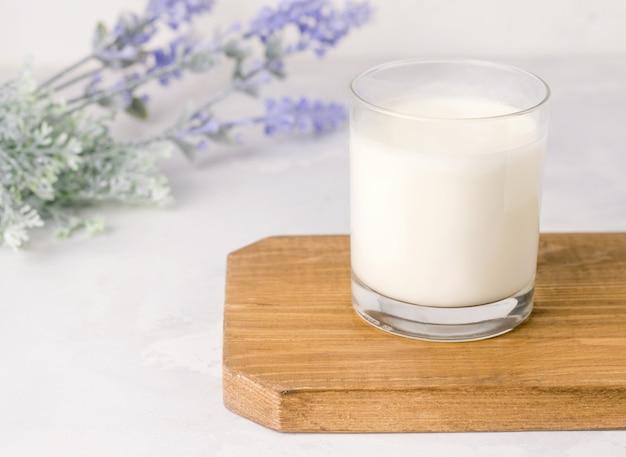 Кефирный напиток ферментированный в стакане на деревянной доске. деревенский