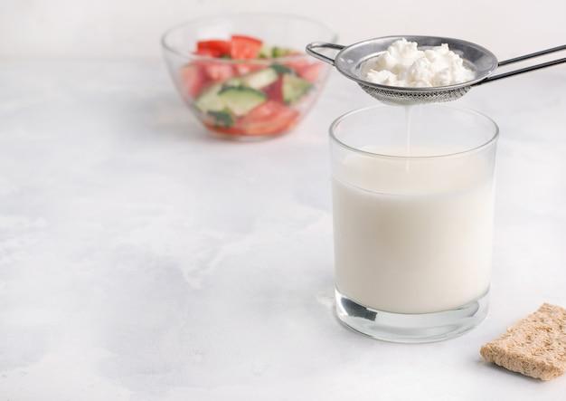 Кефир пьют кисломолочный продукт в стакане. концепция здорового завтрака