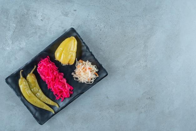 파란색 테이블에 플라스틱 접시에 발효 후추와 소금에 절인 양배추.