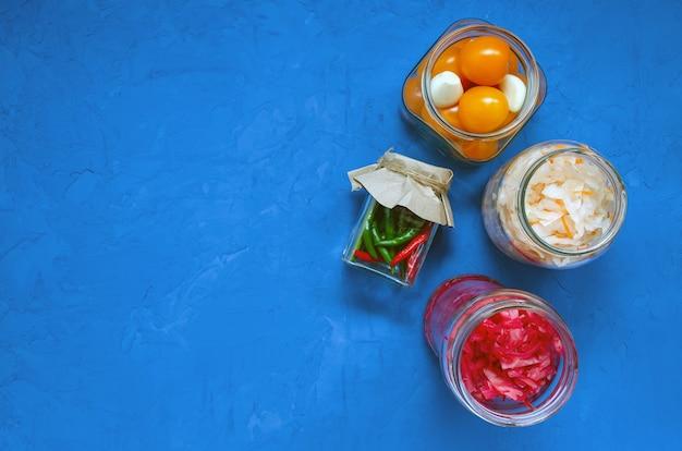 発酵漬物のコンセプト。赤と白のキャベツ、ニンニクと黄色のチェリートマト、古典的な青い背景に異なるガラスの瓶にマルチカラーの唐辛子