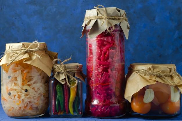 発酵漬物のコンセプト。赤と白のキャベツ、ニンニクと黄色のチェリートマト、古典的な青い壁に異なるガラスの瓶にマルチカラーの唐辛子