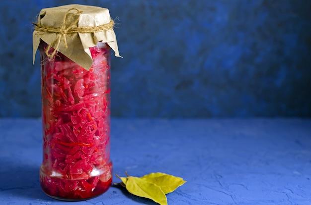 発酵漬物。古典的な青の背景にガラスの背の高い瓶にビーツと月桂樹の葉と赤キャベツ