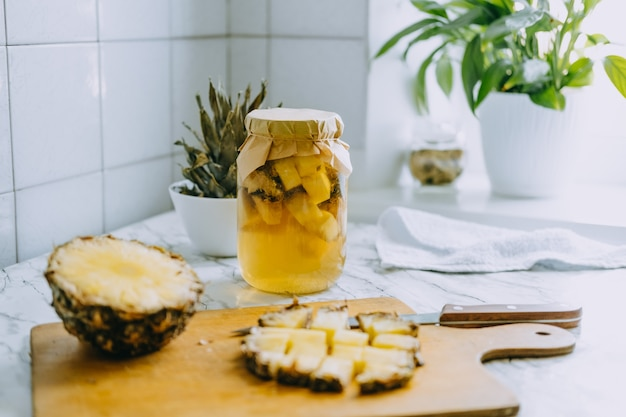 Fermented pineapple kombucha drink tepache. cooking process of homemade probiotic superfood pineapple beverage. drink jar and sliced pineapple on home kitchen.