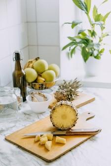 Комбуча из ферментированных ананасов, напиток тепаче. процесс приготовления домашнего ананасового напитка с пробиотиками. банка для питья и нарезанный ананас на домашней кухне.