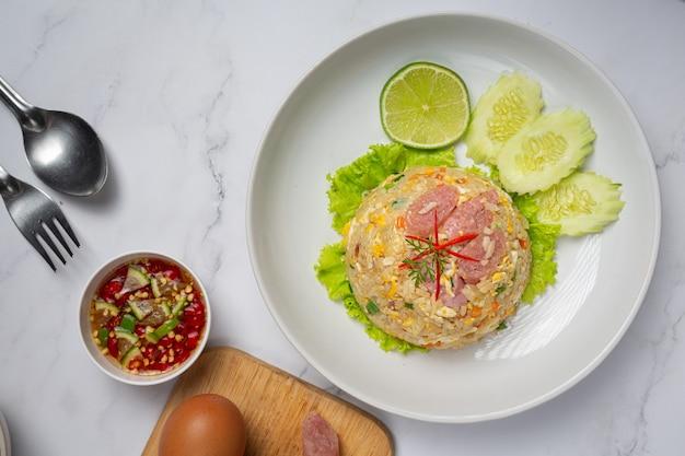 Жареный рис из ферментированной свинины, подается со свежим огурцом