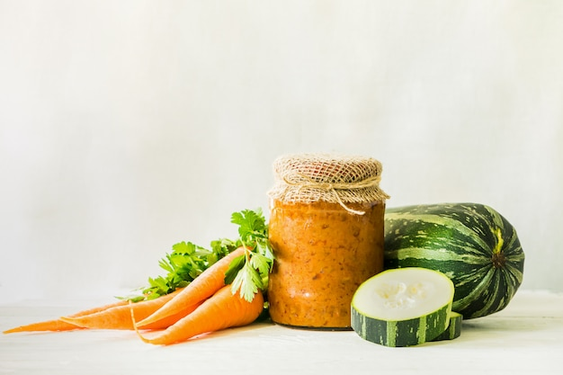 Fermented preserved canning various vegetables zucchini carrots in glass jars on table canned food.