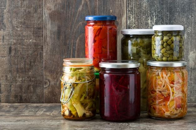 Fermented preserved vegetables in jar on wooden table copyspace