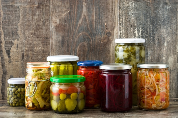 Fermented preserved vegetables in jar on wooden table