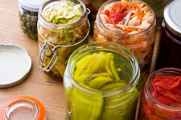 Fermented preserved vegetables in jar on wooden table.