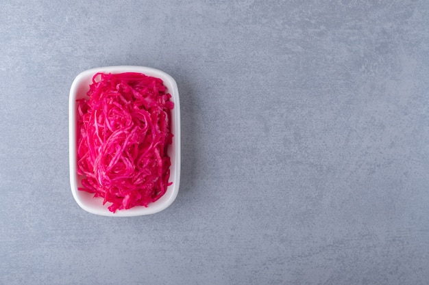 Fermented red cabbage lies in bowl , on the marble background.