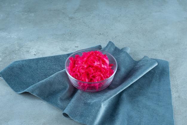 Квашенная краснокочанная капуста лежит в миске на куске ткани, на синем столе.