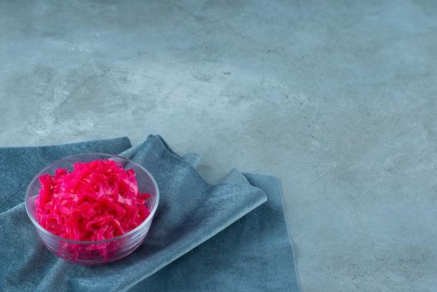 발효된 붉은 양배추는 파란색 탁자 위에 있는 천 조각에 있는 그릇에 놓여 있습니다.