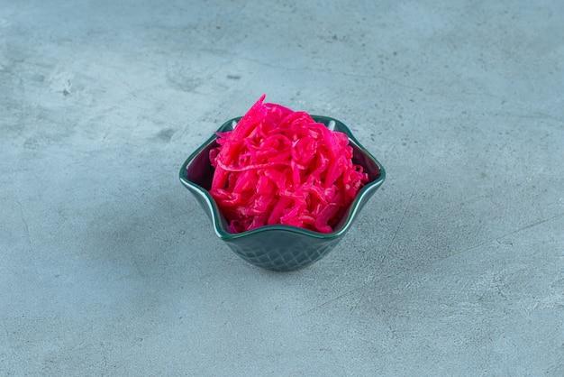 Квашеная краснокочанная капуста лежит в миске на синем столе.