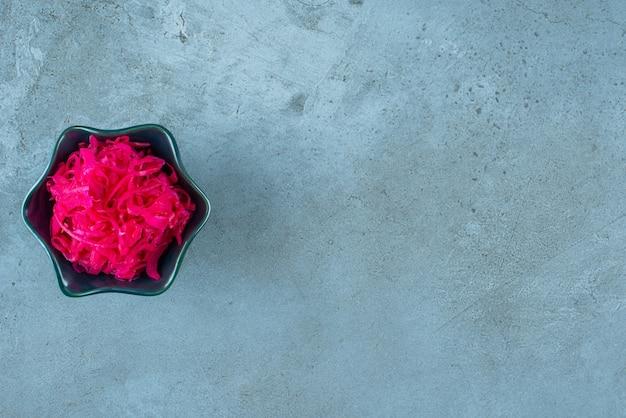 발효된 붉은 양배추는 파란 탁자 위에 있는 그릇에 놓여 있습니다.