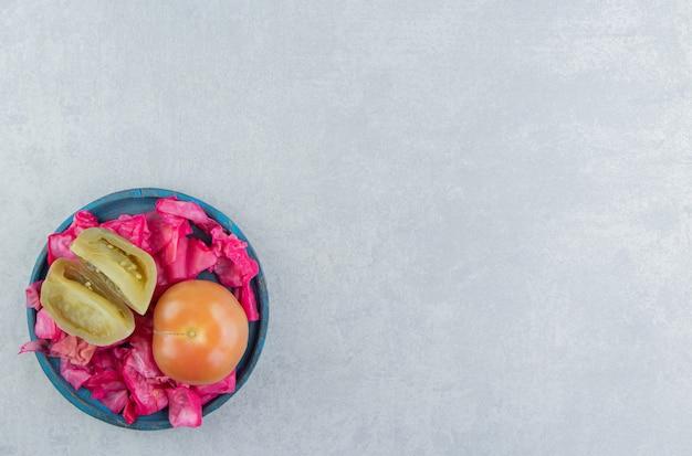 대리석 표면에 있는 나무 접시에 발효된 붉은 양배추, 전체 및 슬라이스 토마토