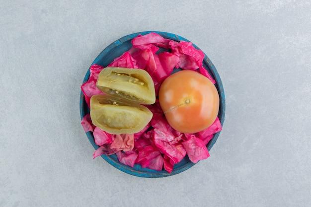 Квашеная краснокочанная капуста, целые и нарезанные помидоры в деревянной тарелке