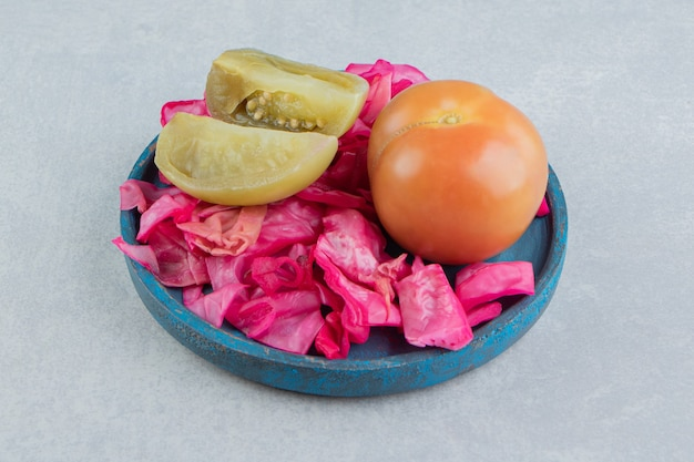 Cavolo rosso fermentato, pomodori interi e affettati in un piatto di legno sulla superficie di marmo