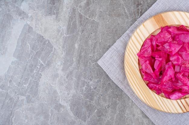 Cavolo rosso fermentato sul piatto di legno.