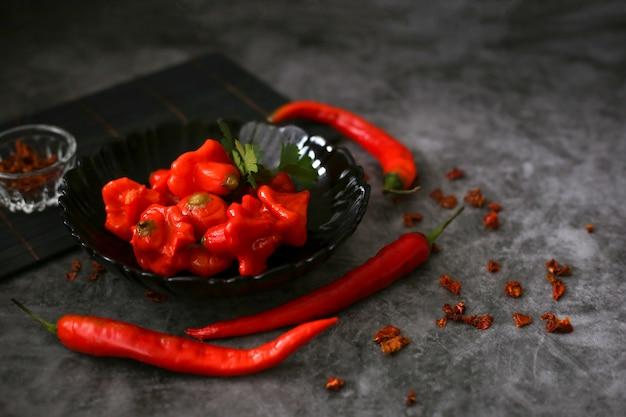 灰色の表面の新鮮な長い赤唐辛子の横にある黒プレートの発酵赤唐辛子