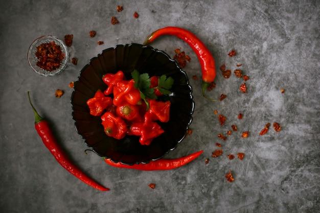 発酵赤唐辛子ビジエ黒プレートと新鮮な唐辛子、灰色の表面、トップビュー