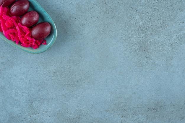 블루 테이블에 접시에 자두와 함께 발효된 붉은 소금에 절인 양배추.