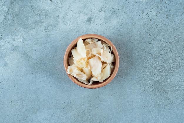 Crauti fermentati con carote in una ciotola, sul tavolo blu.