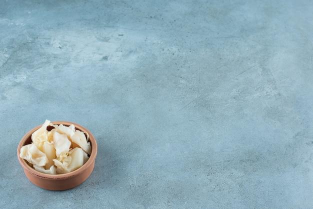 青い表面のボウルにニンジンを入れた発酵ザワークラウト