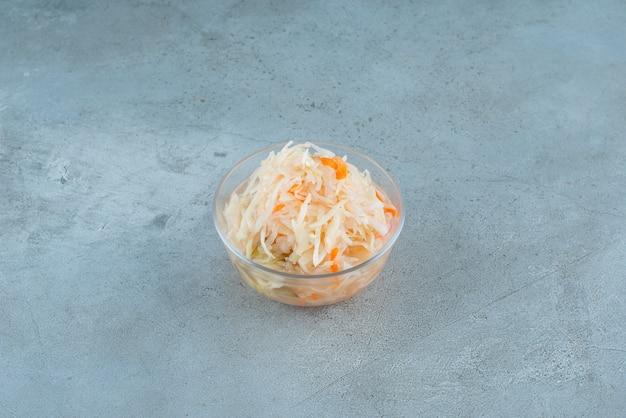 Квашеная капуста с морковью в миске на синем столе.