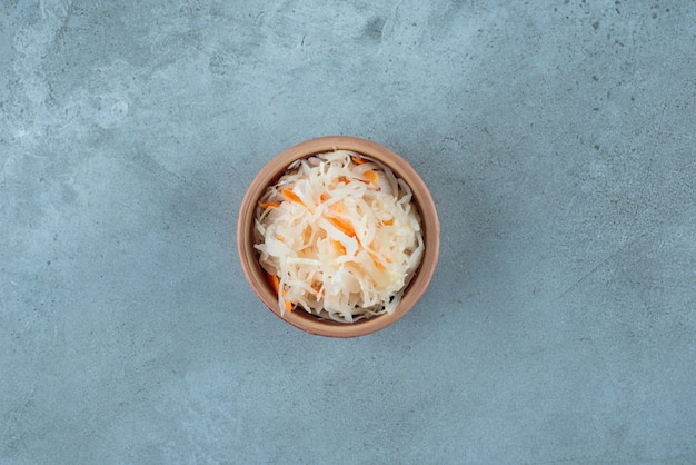 Квашеная капуста с морковью в глиняной миске на синем столе.