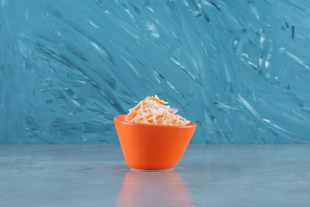 Квашеная капуста с морковью в пластиковой миске на синем столе.