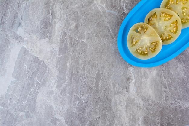 青いプレート上の発酵トマトスライス