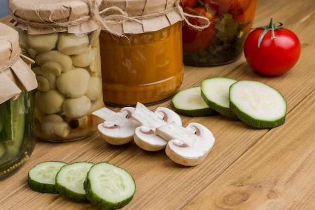 유리 항아리에 발효 야채. 다진 생 야채. 건강한 겨울 영양. 수제 발효 제품. 가벼운 나무 표면입니다.