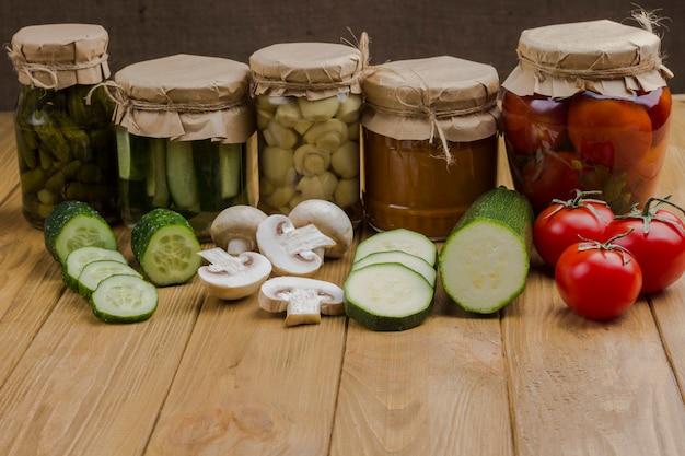 유리 항아리에 발효 야채. 다진 생 야채. 건강한 겨울 영양. 수제 발효 제품. 가벼운 나무 표면. 공간 복사