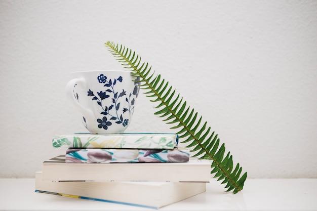 Fern leaf near cup and books