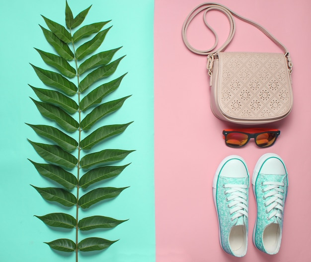 Fern leaf, sneakers, sunglasses, bag on pastel. women's accessories, botanical style, top view, flat lay