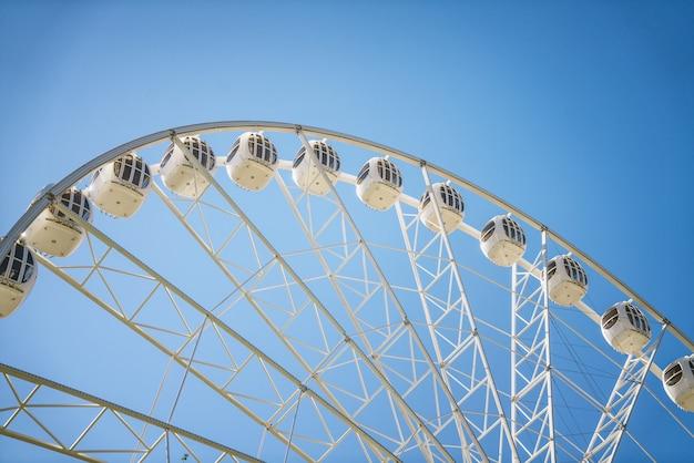 Ferris wheel against the blue sky closeup