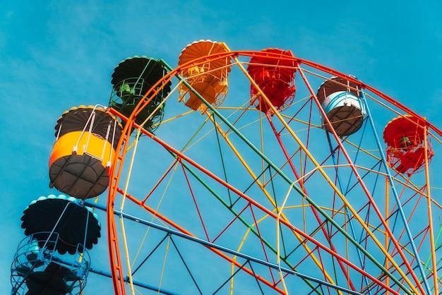 Колесо обозрения против ясного голубого неба в парке развлечений Premium Фотографии