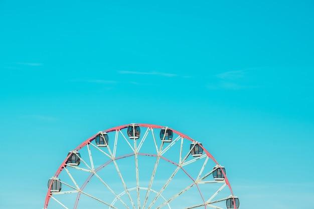 Колесо обозрения на фоне облачного неба. фото крупным планом