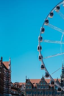 Колесо обозрения против голубого неба в исторической части гданьска польша